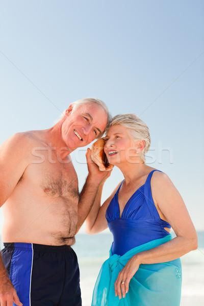 Emekli çift dinleme kabuk plaj gülümseme Stok fotoğraf © wavebreak_media