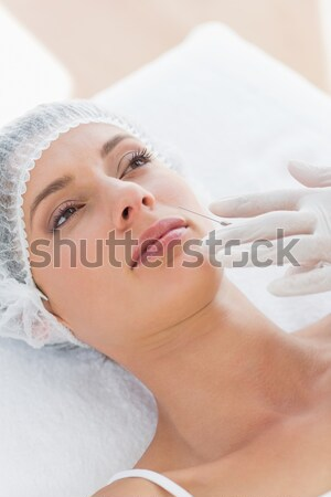 young woman having a forehead massage while looking at the camera Stock photo © wavebreak_media