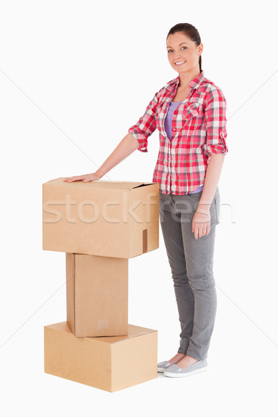 Beautiful woman posing with cardboard boxes while standing against a white background Stock photo © wavebreak_media