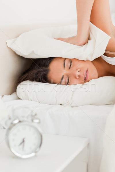 gorgeous woman waking under sheet not wanting to hear alarm clock in bedroom Stock photo © wavebreak_media