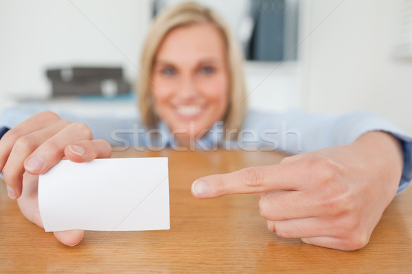 Blonde businesswoman pointing at a card crouching behind her desk in her office Stock photo © wavebreak_media