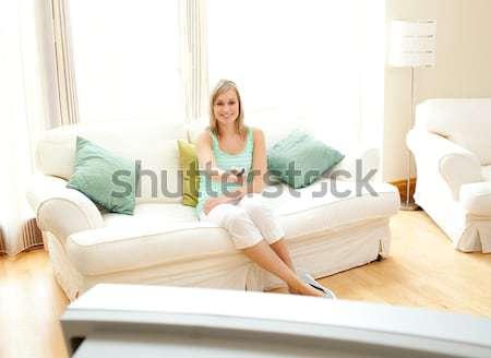 Cute woman sitting on a sofa in her living room Stock photo © wavebreak_media