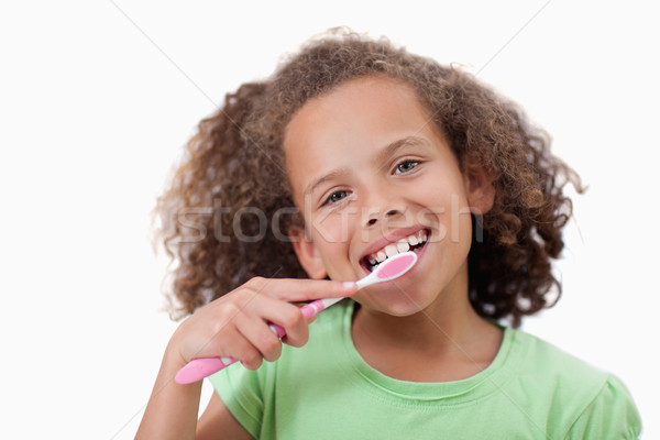 Cute girl brushing her teeth against a white background Stock photo © wavebreak_media