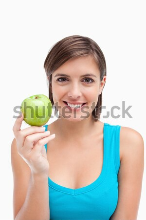 Young woman holding a green apple in her right hand against a white background Stock photo © wavebreak_media