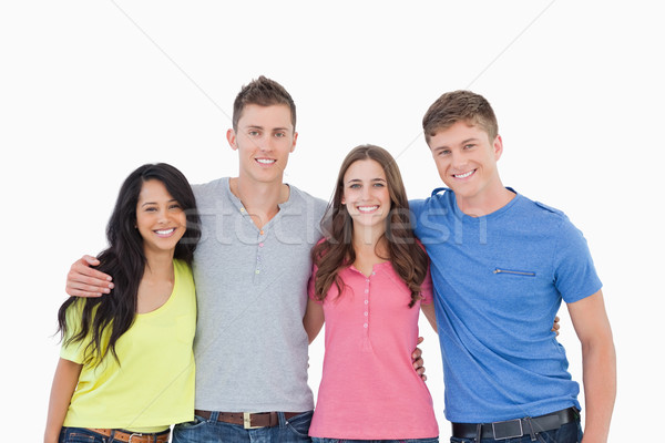 A group of friends standing beside and holding each other as they smile and look into the camera Stock photo © wavebreak_media