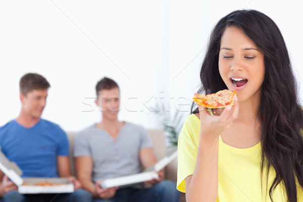 A smiling woman about to eat a slice of pizza as her friends sit behind her  Stock photo © wavebreak_media