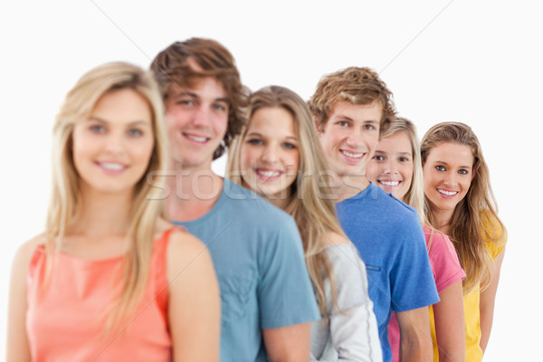 A smiling group standing behind each other at an angle while looking at the camera Stock photo © wavebreak_media