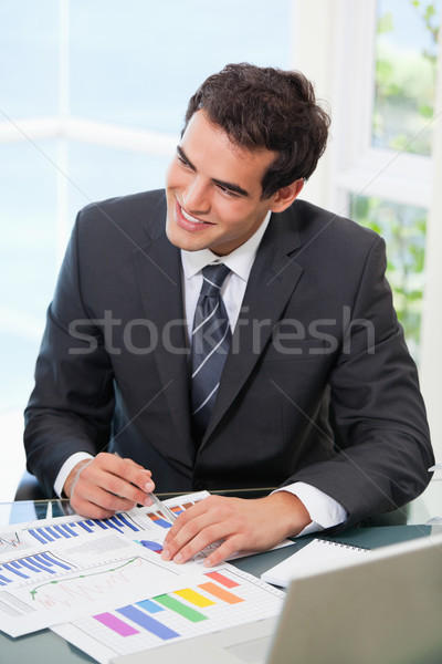 Man pointing out a graph while looking away in an office Stock photo © wavebreak_media