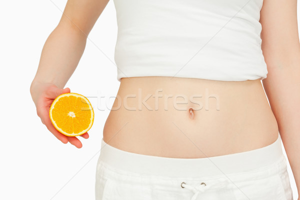 Woman placing an orange next to her belly against white background Stock photo © wavebreak_media