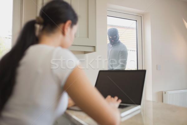 Ladrón mirando mujer usando la computadora portátil cocina vidrio Foto stock © wavebreak_media