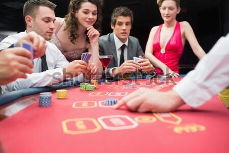 Smiling man claiming the pot in poker game in casino Stock photo © wavebreak_media