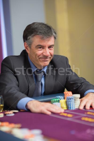 Souriant homme puces roulette table verre Photo stock © wavebreak_media