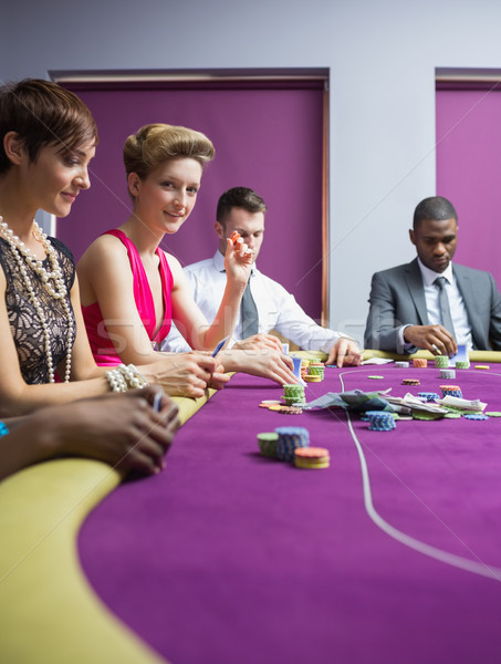 Stock photo: Woman smiling and looking up from poker game in casino