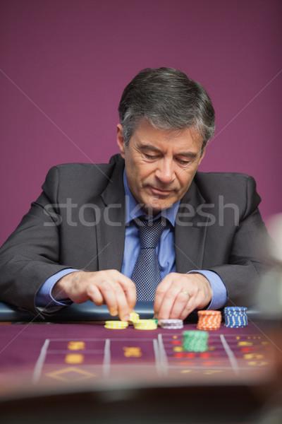 Adam cips oynama rulet oturma tablo Stok fotoğraf © wavebreak_media
