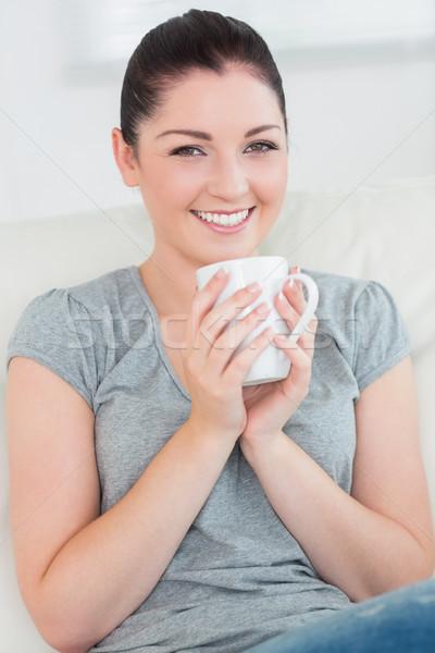Jeunes femme souriante chambre canapé mug Photo stock © wavebreak_media