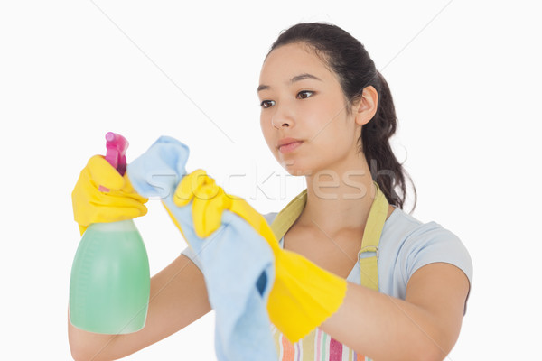 Woman wiping surface with cloth wearing apron and rubber gloves Stock photo © wavebreak_media