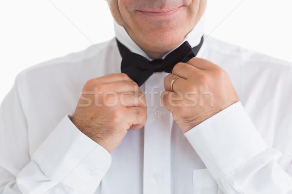 Smiling man fixing bow tie on white background Stock photo © wavebreak_media
