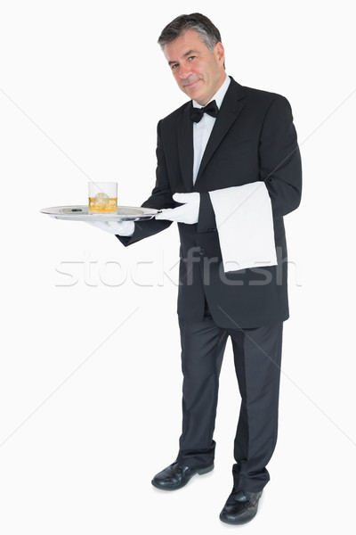 Smiling waiter offering whiskey with ice on tray Stock photo © wavebreak_media