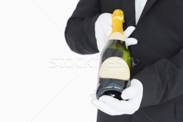 Waiter presenting champagne bottle on white background Stock photo © wavebreak_media