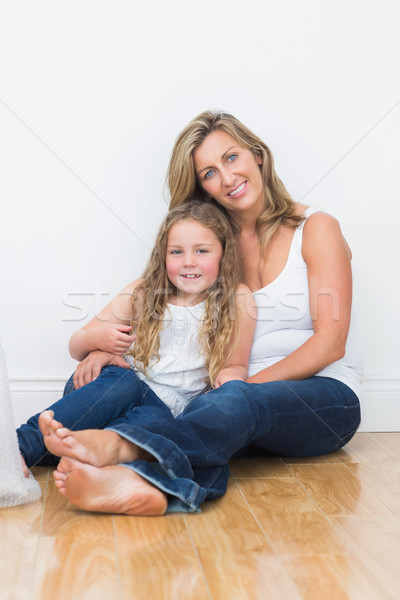 Happy mother and daughter sitting on the floor and directly looking into the camera Stock photo © wavebreak_media