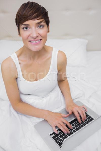 женщину ноутбука улыбающаяся женщина кровать компьютер Сток-фото © wavebreak_media