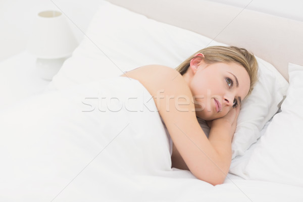 Thoughtful young woman lying in bed Stock photo © wavebreak_media