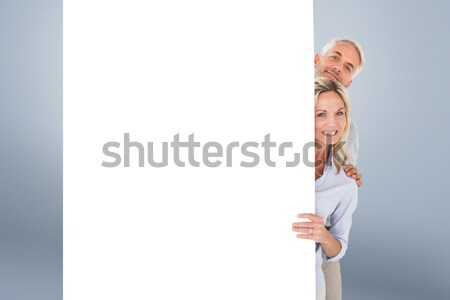 Composite image of happy couple showing large poster Stock photo © wavebreak_media