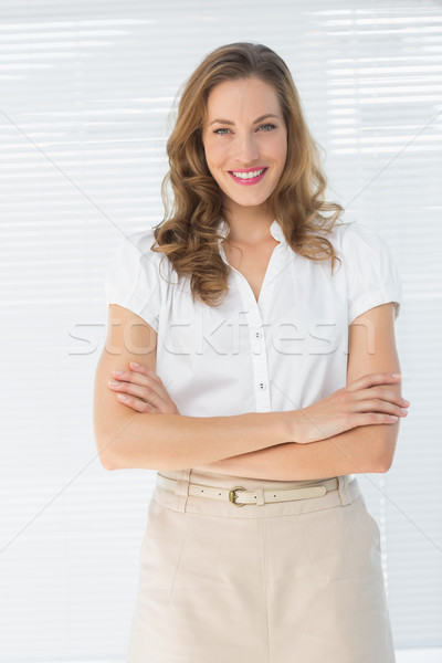 Smiling businesswoman with arms crossed against blinds Stock photo © wavebreak_media