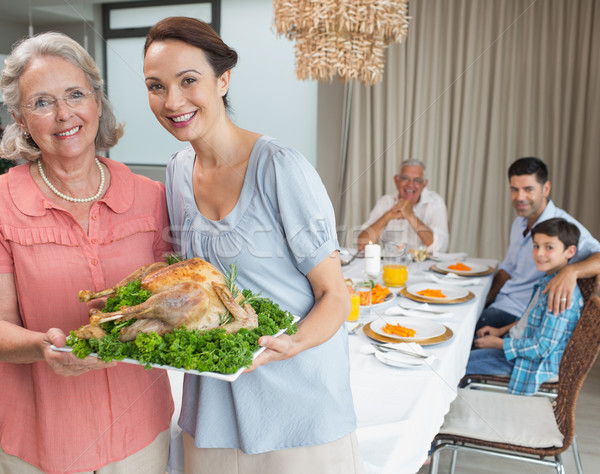 Woman and grandmother holding chicken roast with family at dinin Stock photo © wavebreak_media
