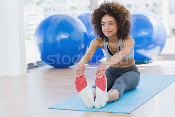 Sporty woman stretching hands to legs in fitness studio Stock photo © wavebreak_media