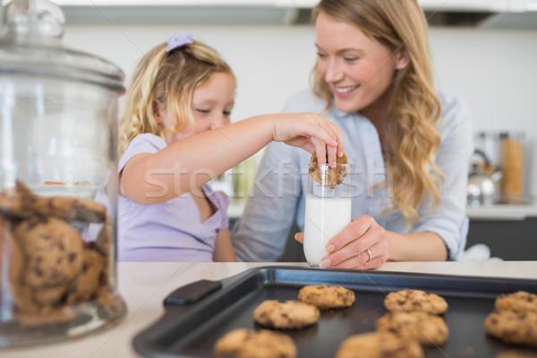 Woman with daughter dipping cookie in milk Stock photo © wavebreak_media