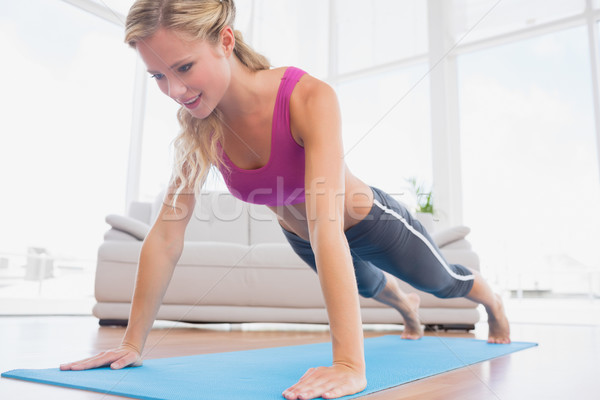 Stock photo: Strong blonde in plank position on exercise mat