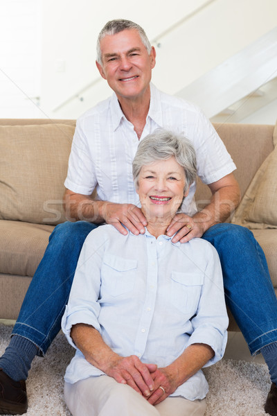 Man giving his relaxed senior wife a shoulder rub smiling at cam Stock photo © wavebreak_media