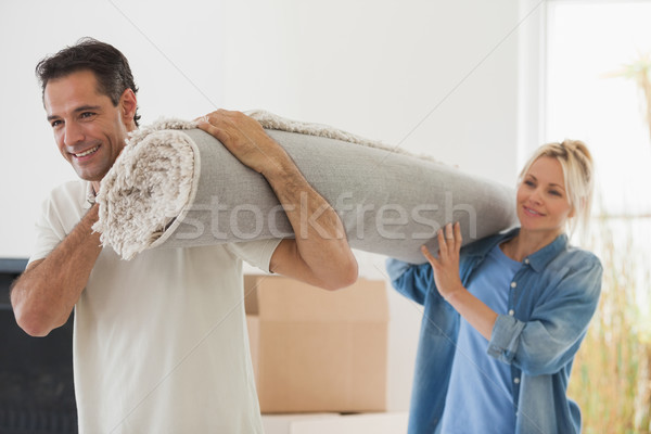 Couple carrying rolled rug after moving in a house Stock photo © wavebreak_media