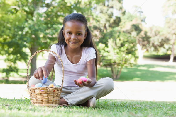 Little girl sitting on grass counting easter eggs smiling at cam Stock photo © wavebreak_media