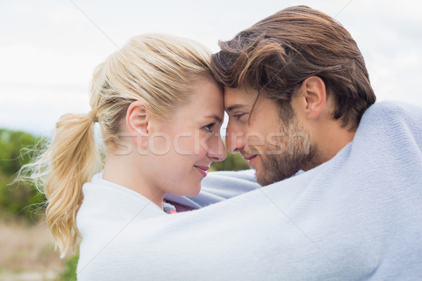 Cute affectionate couple standing outside wrapped in blanket Stock photo © wavebreak_media