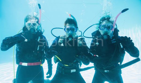 Friends on scuba training submerged in swimming pool making ok s Stock photo © wavebreak_media