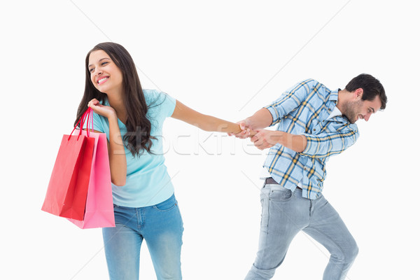 Attractive young man pulling his shopaholic girlfriend Stock photo © wavebreak_media