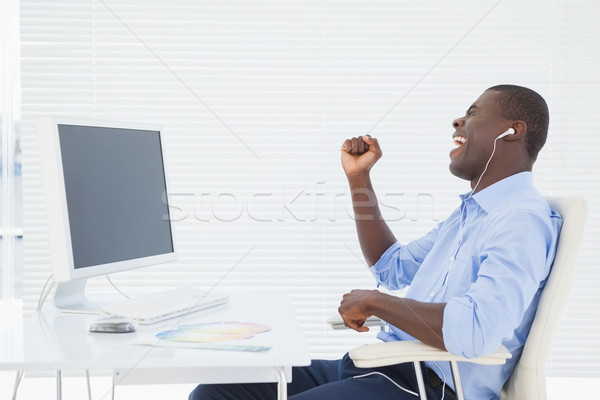 Stock photo: Businessman listening to music while he works