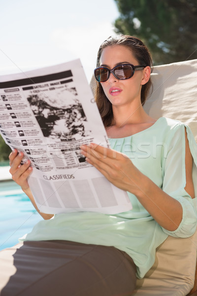 Woman reading newspaper on sun lounger by pool Stock photo © wavebreak_media