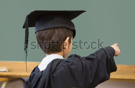 Cute pupil in graduation robe pointing in classroom Stock photo © wavebreak_media