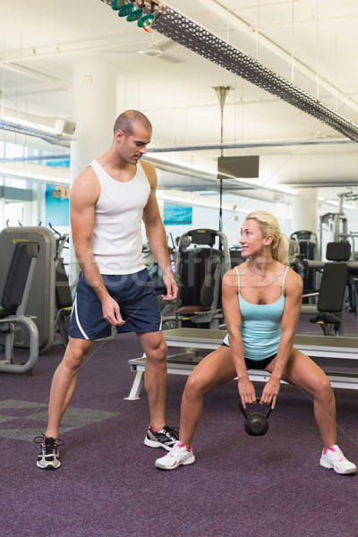 Trainer assisting woman with kettle bell in gym Stock photo © wavebreak_media