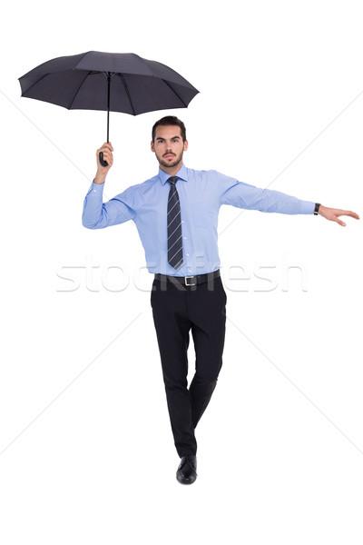 Focused businessman with umbrella balancing Stock photo © wavebreak_media