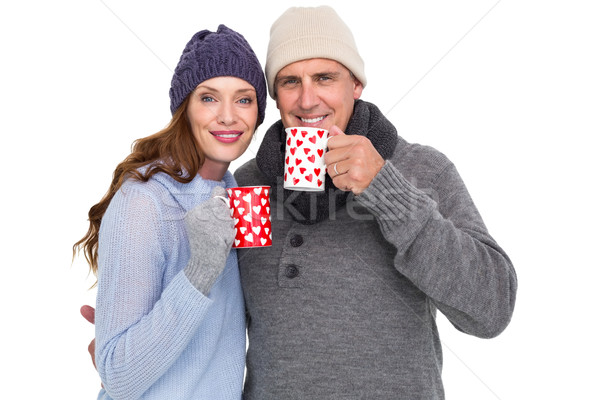 Happy couple in warm clothing holding mugs Stock photo © wavebreak_media