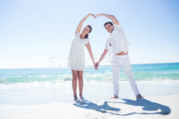 Happy couple forming heart shape with their hands Stock photo © wavebreak_media
