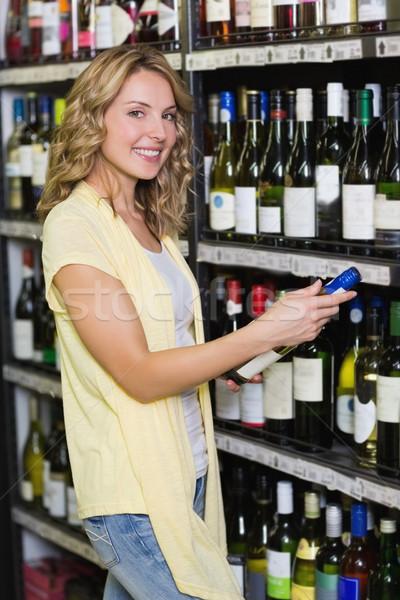 Portrait of smiling pretty blonde woman looking at wine bottle  Stock photo © wavebreak_media