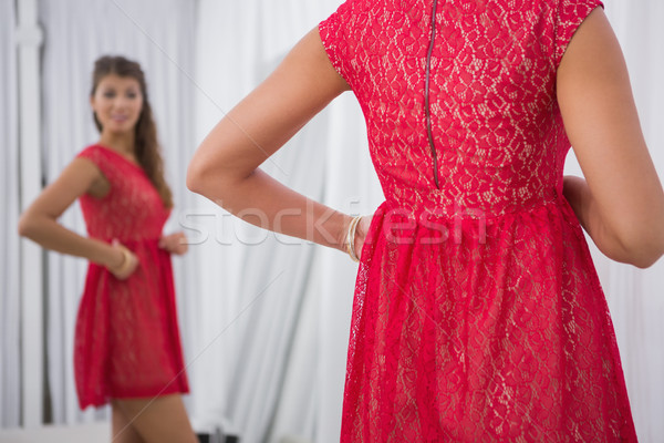 Smiling woman trying on a red dress Stock photo © wavebreak_media