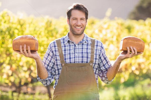 Smiling farmer holding two tasty breads Stock photo © wavebreak_media