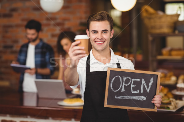 Smiling barista holding take-away cup and open sign  Stock photo © wavebreak_media