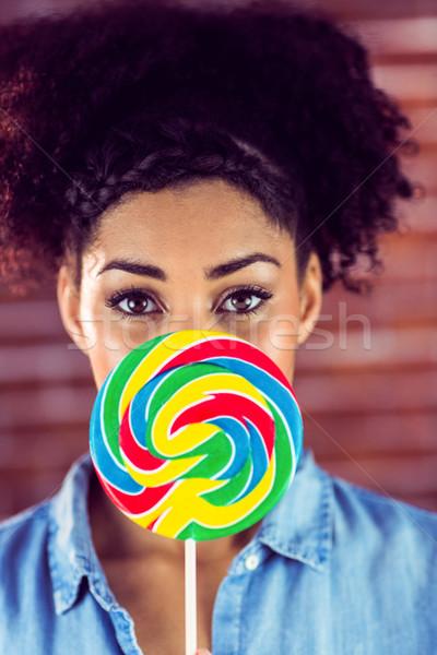 Portrait of a beautiful woman hiding behind a giant lollipop  Stock photo © wavebreak_media